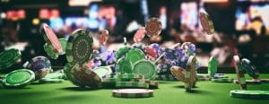 Poker chips falling on green felt roulette table, blur casino interior background.
